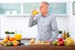 Mature man drinking orange Juice in the kitchen II