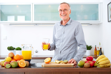 Mature man with a glass of orange Juice in the kitchen, smiling