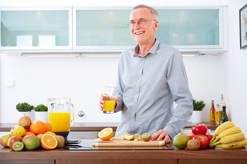 Mature man with a glass of orange Juice in the kitchen