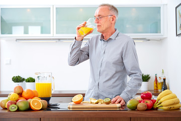 Mature man drinking orange Juice in the kitchen II