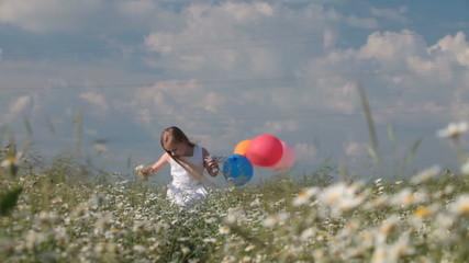 Little girl with balloons walking through flowering summer field
