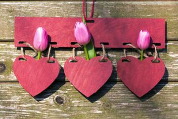 Drei Herzen mit rosa Tulpen vor Holz