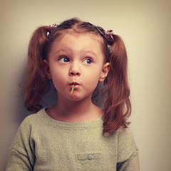 Fun girl eating candy with surprising thinking big eyes. Vintage