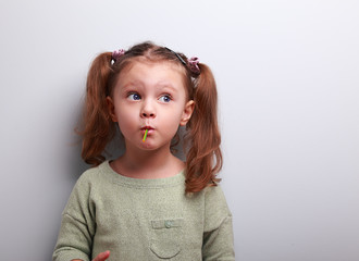 Funny thinking kid girl eating lollipop and looking up