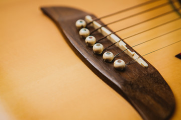 Macro shot down the fretboard of acoustic guitar