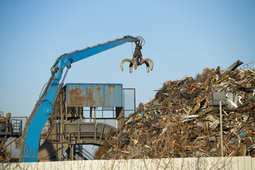 Crane claw on top of pile with scrap metal in recycling center