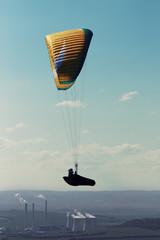 Paraglider flying over power station at sunset