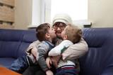 Grandchildren kissing their grandmother