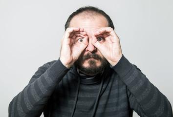 Shocked man looking through hands, making binoculars