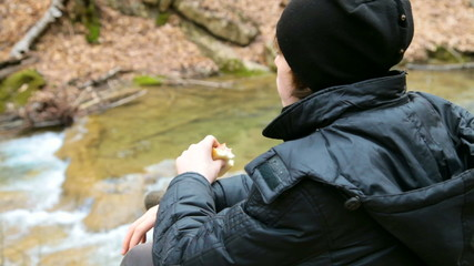 Hiking boy having lunch on nature in the woods near river