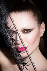 woman with pink lips and lace on black background. in studio