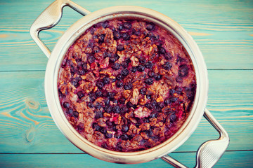 oatmeal, walnut and black currant casserole in pan on blue table