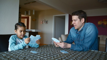 Happy young girl playing cards with her dad