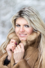 Young woman in fur coat at winter outdoor.