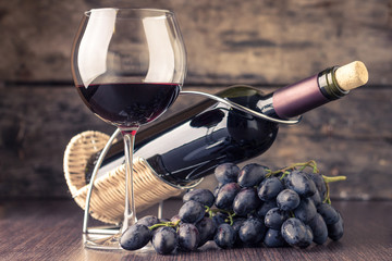 Winery background. Wineglass with bottle of red wine