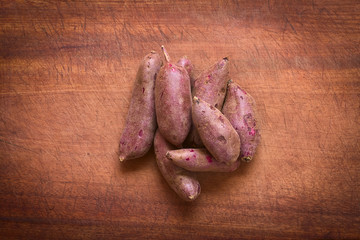 Raw purple sweet potato (lat. Ipomoea batatas) on wood