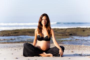 Schöne, schwangere Frau sitzt am Strand im Sand