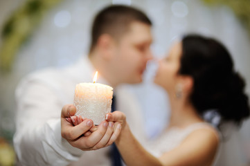 the bride and groom are holding a beautiful candle
