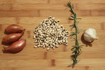Beans, onions, rosemary and garlic on a wooden backround