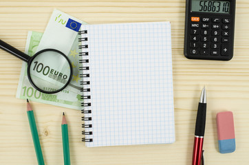 Office, business tools with notebook and euro on wooden table