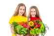 Smiling girls with basket of vegetables