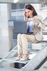Shocked young businesswoman working on laptop