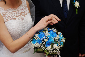 bride groom wears a wedding ring on the finger
