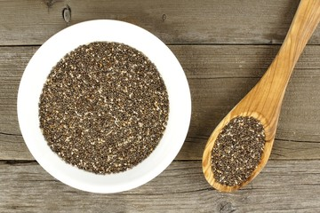 Bowl and spoon filled with chia seeds over a wood background