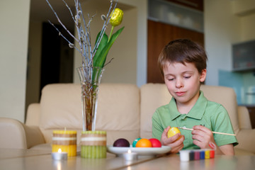 Little toddler boy painting colorful Easter egg