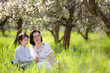 Young woman and her child in spring apple garden