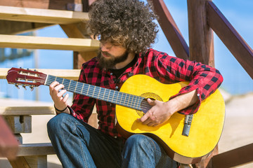 Guitarist with plaid shirt and afro hair