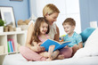 Mother reading with children at bedtime