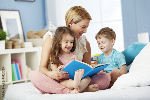Mother reading with children at bedtime Poster