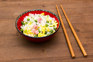 Cantonese rice with chopsticks on wooden table
