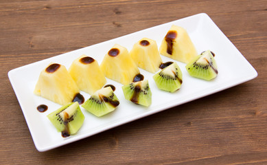 Pineapple and kiwi with balsamic vinegar on wooden table