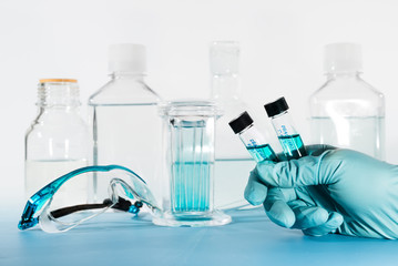 Liquid samples in gloved hand, laboratory
