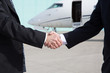 Businessmen shake hands in front of a corporate jet - 79928526