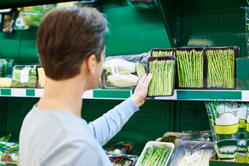 Man buys asparagus in store