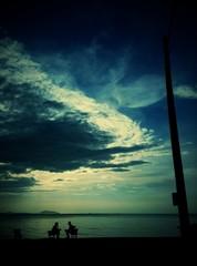 2 friends talking under cloudy sky at seaside