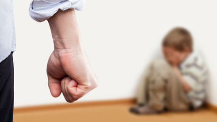 Angry man raised fist over wall corner sitting child boy