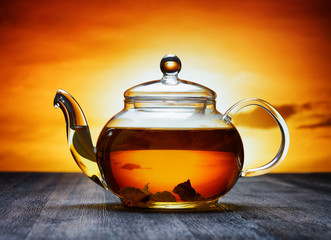 Glass teapot of fresh aromatic tea on a black wooden table and o
