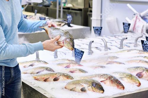 Man chooses carp fish in supermarket - 79932955
