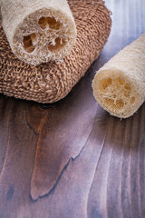 two loofahs and brown batch bast on vintage wooden board
