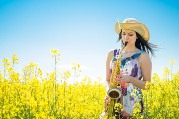 Woman playing saxophone in rapeseed field