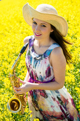 Woman with saxophone in rapeseed field