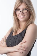 Junge Frau mit Brille lächelt unsicher