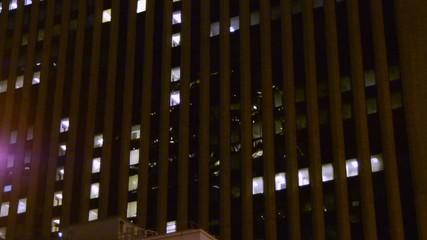 Establishment shot of a city skyscraper at night