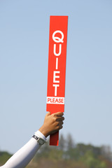 The quiet please sign was held up by volunteer in golf tournamen