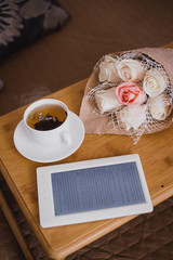 Wooden tray with tea, flowers and e-book standing on a bed