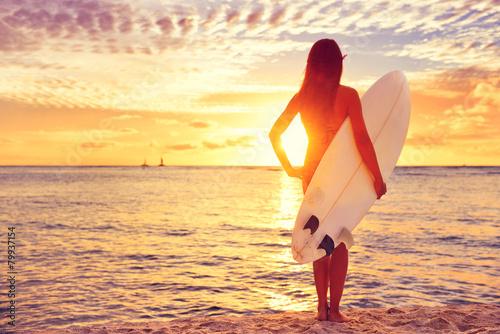 Surfer girl surfing looking at ocean beach sunset - 79937154
